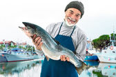 Fisher holding a big atlantic salmon fish — Stock Photo