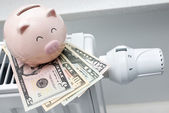 Heating thermostat with piggy bank and money — Stock Photo