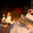 Reading book by fireplace — Stock Photo #36662141