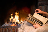 Reading book by fireplace — Stockfoto
