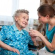 Senior woman with home caregiver — Foto Stock #38571691