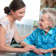 Senior woman with home caregiver — Stockfoto