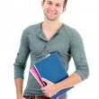 Smiling teenager with schoolbooks and hand in pocket — Stock Photo