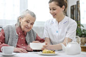 Senior woman with home caregiver — Foto Stock