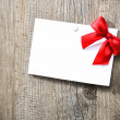 Greeting card with red ribbon — Stock Photo