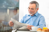Senior man with a newspaper — Stock Photo