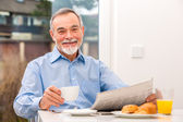 Senior man with a newspaper — Stock Photo