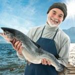 Fisher holding a big atlantic salmon fish — Stock Photo