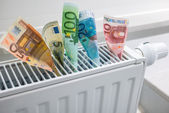 Heating thermostat with money — Stock Photo