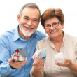 Senior couple holding a house model and piggy bank — Stock Photo