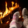 Feet in wool socks warming at the fireplace — Stock Photo #49213847