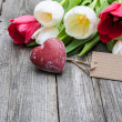 Fresh tulips and red heart with a tag — Stock Photo #49214023