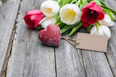 Fresh tulips and red heart with a tag — Stock Photo