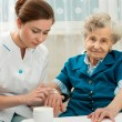 Elderly woman is assisted by nurse at home — Stock Photo