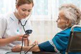 Measuring blood pressure of senior woman — Stock Photo