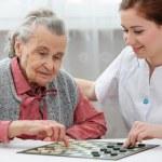 Senior woman playing checkers — Stock Photo
