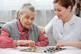 Senior woman playing checkers — Stock Photo