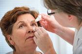 Senior woman applying eye drops — Stock Photo