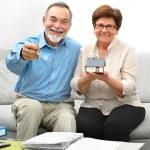 Happy senior couple holding a small house — Stock Photo