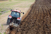 Tractor plowing the field — Photo