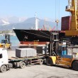 Commercial harbor with truck forklift and ship - Stock Photo