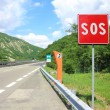 Emergency phone and sos sign on road — Stock Photo
