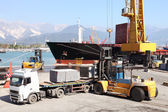 Commercial harbor with truck forklift and ship — Stock Photo