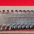 Row of empty shopping carts in supermarket - Stock Photo