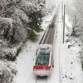 Passenger train moving along snow track — Stock Photo