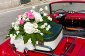 Floral wedding bouquet on vintage car — Stock Photo