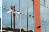Three security cameras on front of glass building — Stock Photo