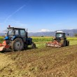 Tractors plowing a field - Stock Photo
