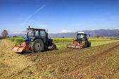 Tractors plowing a field — Photo