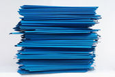 Stacks of blue folders over white background — Stock Photo