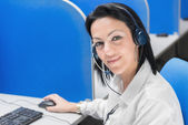 Smiling call center operator girl sitting at desk with computer — Stock Photo