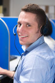 Call center operator with headset smiling — Stock Photo