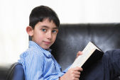 Young boy reading book — Stockfoto