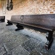 Wooden bench in old church courtyard — Stock Photo #42569359