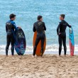 Cannes, France - APRIL 27, 2014: four young surfers waiting the right wave on the beach. — Stock Photo