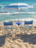 Beach umbrella and chairs on the sea shore — Stock Photo