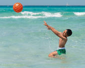 Child playing with ball in the turquoise sea — Photo