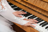 Bride plays the piano — Stock Photo