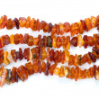 Beads of raw amber on white - Stock Photo