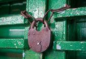 Old rusty lock on a wooden door — Stock Photo