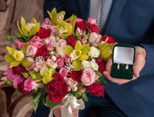 Bridal bouquet and the ring in the hands of the groom — Стоковое фото