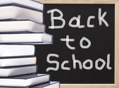 Books with back to school chalkboard text background — Stock Photo