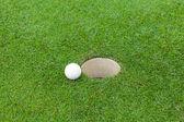 Golfball auf lippe cup — Stockfoto