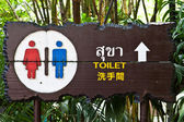 Sign of public toilet in three languages, Thai, English, and Chi — 图库照片