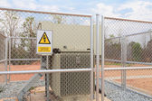 Danger High Voltage sign on a fence — Stock Photo
