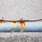 Rusty barbed wire on a metal tube — Stock Photo